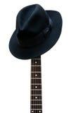 Chapeau de cru se reposant sur un fretboard de guitare Photographie stock libre de droits