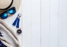 Chapeau de l'été de la femme, coquille, roues sur le fond en bois blanc, configuration plate, vue supérieure Bases de déplacement images stock