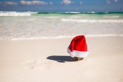 Chapeau de Noël à la noix de coco sur une plage sablonneuse blanche Images libres de droits