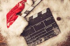 Chapeau de Noël avec le panneau de film dans la neige photographie stock