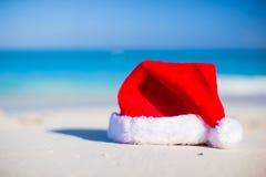 Chapeau de Noël de plan rapproché sur une plage sablonneuse blanche Image stock