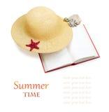 Chapeau de paille avec le livre et les étoiles de mer rouges d'isolement Photographie stock