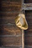 Chapeau de paille de cowboy contre le bois superficiel par les agents Photographie stock