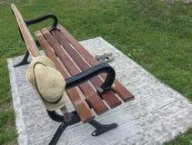 Chapeau de paille du ` s de femmes accrochant sur le banc et les chaussures de parc en bois près de lui Images stock