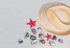 Chapeau de paille en osier d'été de vintage avec le ruban coloré sur la plage avec les pierres décoratives et les étoiles de la M photo libre de droits
