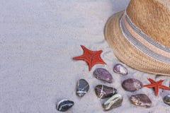 Chapeau de paille en osier de vintage avec le ruban coloré sur la plage avec les pierres décoratives et les étoiles de la Mer Rou photo libre de droits