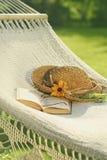 Chapeau de paille et livre sur l'hamac de dentelle Photographie stock