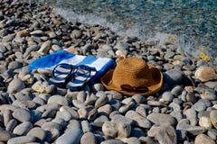 Chapeau de paille, lunettes de soleil, bascules électroniques, serviette sur un paysage marin de fond Image libre de droits