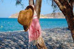 Chapeau de paille, serviette sur un paysage marin de fond Photos stock