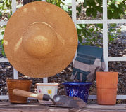 Chapeau de paille sur le treillis avec des pots et des outils de yard Photographie stock libre de droits