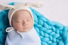 Chapeau de port adorable d'oreilles de lapin d'enfant nouveau-né dormant sur un lit image stock