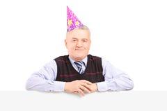 Chapeau de port de partie de monsieur et pose derrière un panneau Image stock