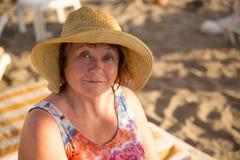 Chapeau de port de sourire de femme supérieure à la plage sur le lit pliant photo stock
