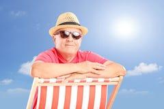 Chapeau de port de sourire et lunettes de soleil d'homme mûr, posant sur une plage image stock
