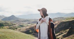 Chapeau de port et poncho de jeune belle voyageuse de femme détendant sur le dessus de la colline image libre de droits