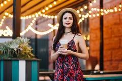 Chapeau de port et robe de femme mignonne de brune, se tenant au cafétéria, tenant la tasse de papier avec du café ou le thé Jeun photographie stock