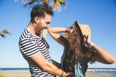 Chapeau de port de femme heureuse riant avec son ami Photographie stock