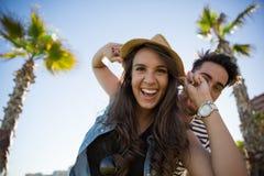 Chapeau de port riant de femme et son ami derrière elle Photo stock
