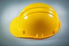 Chapeau de sécurité jaune sur le concept concret de construction de fond Photos stock