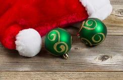 Chapeau de Santa avec les ornements verts sur les conseils en bois Photographie stock