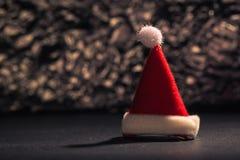 Chapeau de Santa Claus devant le fond de scintillement Photographie stock