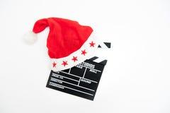 Chapeau de Santa Claus sur un panneau de clapet de film Images libres de droits