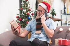 Chapeau de Santa d'usage d'homme de l'Asie et boîte-cadeau et d'utilisation entretien mobile de se tenir Photographie stock libre de droits
