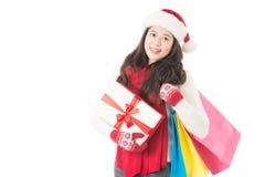Chapeau de Santa de femme et cadeaux de port de pensée de se tenir Image stock