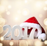 Chapeau de Santa sur le fond en bois rustique avec les schémas 2017 Photographie stock libre de droits
