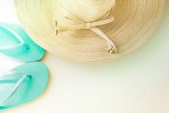 Chapeau de Sun de femmes élégantes avec les pantoufles bleues de plage d'arc sur le fond blanc Relaxation de vacances de bord de  photos libres de droits