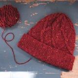 Chapeau de tweed tricoté par rouge avec un modèle Photo stock