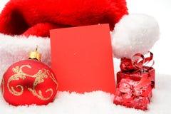 Chapeau du père noël de Noël avec la carte de souhaits en rouge sur la neige Photographie stock libre de droits