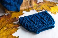 Chapeau et aiguilles bleus tricotés de laine sur la table blanche Photographie stock