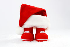 Chapeau et bottes de Santa Claus sur la neige devant le fond blanc Photo libre de droits