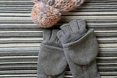 Chapeau et gants de laine sur un fond de tricotage rayé Photo stock