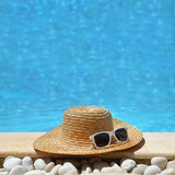 Chapeau et lunettes de soleil par le poolside Image stock