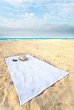 Chapeau et lunettes de soleil sur un essuie-main sur la plage avec le Dr. Photographie stock libre de droits
