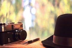 Chapeau et rétro appareil-photo de photo sur le fond de l'été de départ Photographie stock libre de droits