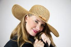 Chapeau femelle blond mûr de portrait de plan rapproché et manteau noir Photographie stock libre de droits