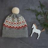 Chapeau gris d'hiver avec un modèle de jacquard sur un fond gris avec un cheval en bois Image libre de droits