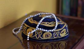 Chapeau islamique de prière et rosemaryt de perles d'isolement sur le fond réfléchi Image stock