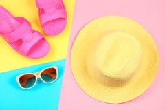 Chapeau, lunettes de soleil et pantoufles sur un fond en pastel de trois-couleur de bleu, de jaune et de rose Image libre de droits