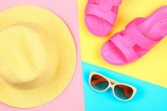 Chapeau, lunettes de soleil et pantoufles sur un fond en pastel de trois-couleur de bleu, de jaune et de rose Images stock