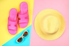 Chapeau, lunettes de soleil et pantoufles sur un fond en pastel de trois-couleur de bleu, de jaune et de rose Photo libre de droits