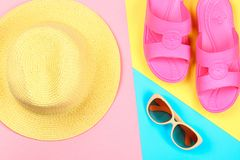 Chapeau, lunettes de soleil et pantoufles sur un fond en pastel de trois-couleur de bleu, de jaune et de rose Photographie stock libre de droits