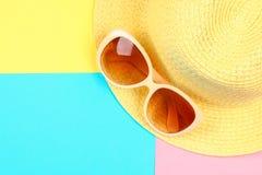 Chapeau, lunettes de soleil sur un fond en pastel de trois-couleur de bleu, de jaune et de rose Image libre de droits