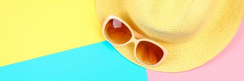 Chapeau, lunettes de soleil sur un fond en pastel de trois-couleur de bleu, de jaune et de rose Images stock