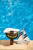 Chapeau marin sur un télescope et un bateau à côté de la piscine Images stock