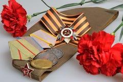 Chapeau militaire soviétique avec les fleurs rouges, ruban de St George, médailles de grande guerre patriotique Photos libres de droits