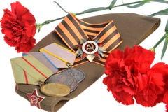 Chapeau militaire soviétique, fleurs rouges, ruban de St George, médailles de grande guerre patriotique Photographie stock libre de droits